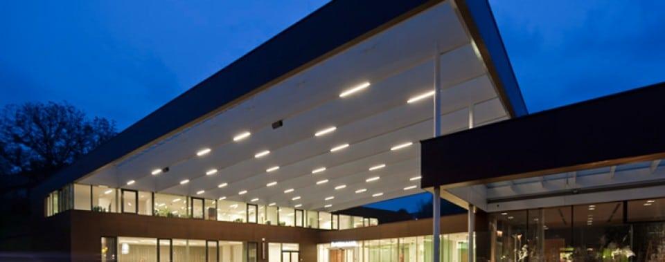 Gemeindezentrum Lannach bei Nacht. Fassade mit Fassadenplatten Farbe kernbraun.