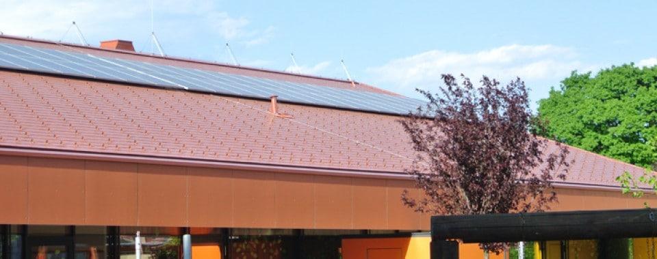 Rote Dachfläche Kindergarten mit oranger Fassade.