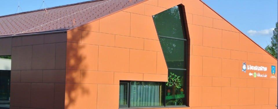 Orange Fassade Kindergarten Frauental mit roter Dachfläche.