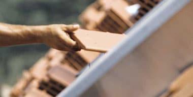 Arbeiter tauscht Dachziegel aus.