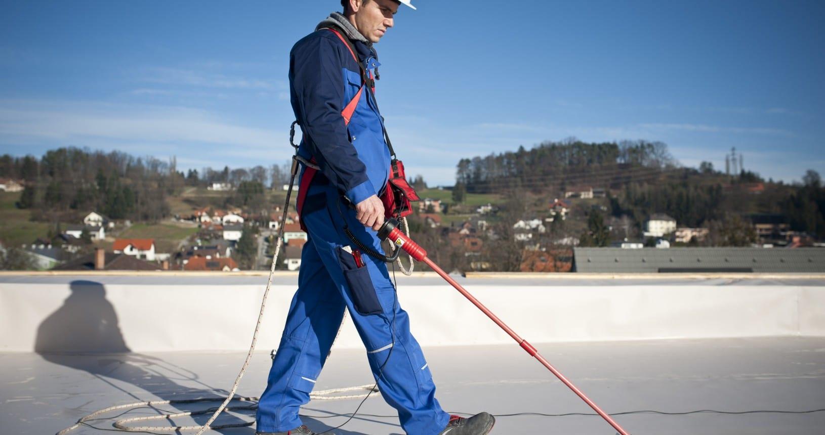 Ein Prüfdach-Arbeiter untersucht ein Foliendach mithilfe des Funkenschlagverfahrens auf Fehler.