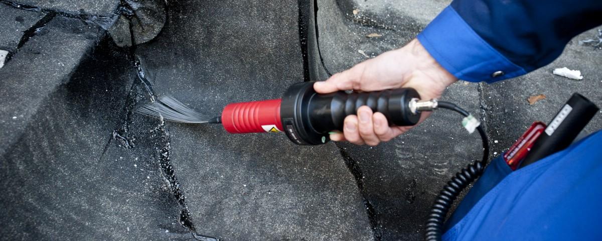 Mitarbeiter der Firma Griessdach untersucht ein Bitumendach mit Strom auf Fehler im Rahmen des Funkenschlagverfahrens.